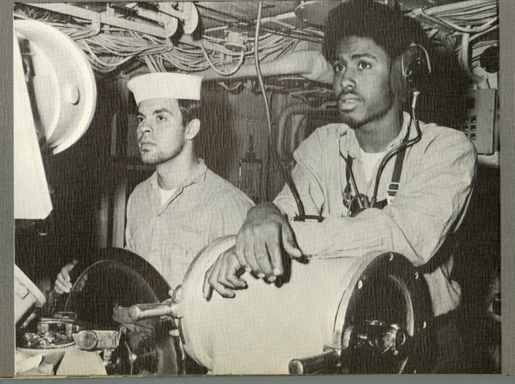 Black and white image of two men standing at helm, a light-skinned man grasps a wheel and a dark-skinned man wearing headphones rests his arms on a cylindrical drum.