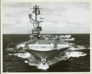 Black and white photo of Aircraft carrier Intrepid sails through the ocean directly toward the camera, surrounded by a foamy white wake, with jet planes on the rear of the flight deck.