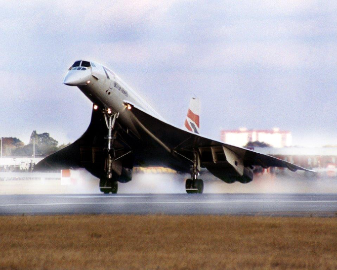 Photo of the front view of a Concorde as it lands on the rear wheels of its landing gear. The plane is tilted up, with the front wheel still in the air, and the nose cone tilted down.