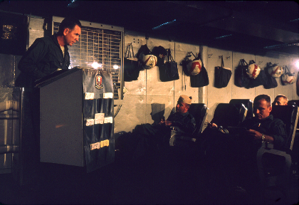 Color photo of a man standing at a podium addressing three men seated in chairs in front of him, helmets and bags hang from the wall in the background.