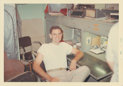 Colored image of a man seated in a chair smiling at the camera with his left arm resting on a desk, a typewriter is on the shelf above his head.