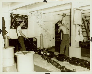 Black and white photo of two men on either side of anchor chain, one man holds rope attached to chain and other raises a large hammer.