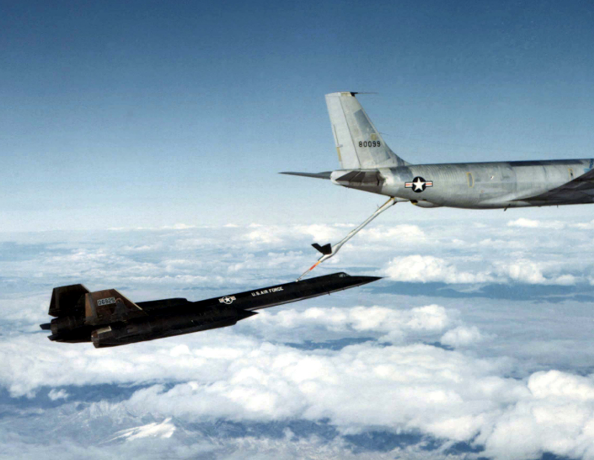A black A-12 jet flies over clouds; a fuel line running from its top is connected to back of a larger grey jet plane that is partially visible above it.