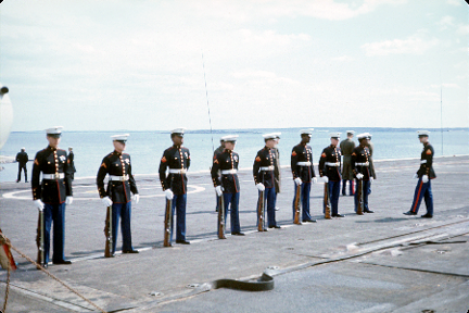 Color photo of eight Marines wearing dress uniforms standing in a line on the flight deck of USS Intrepid.
