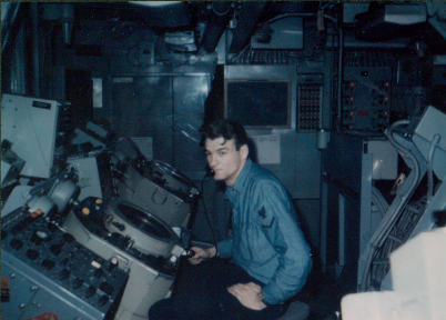 Color photo of a man wearing blue work uniform seated in front of radar equipment looking at the camera.