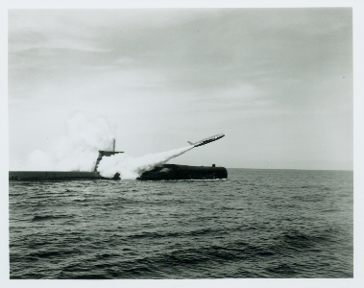 Black and white photo of USS Growler above water launching Regulus I missile into the air, cloud trail extends behind missile partially obscuring submarine.