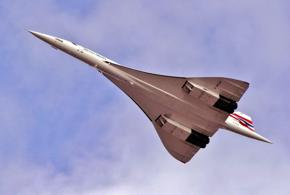A photo of the Concorde as it flies directly overhead, toward the top left corner of the frame. It is pointed at the front and its triangular delta wings extend out starting a quarter of the way from the front.