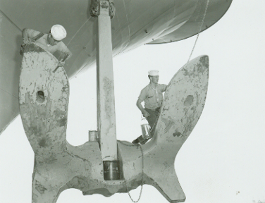 Black and white photo of large hanging anchor with two sailors on each side of the anchor, scraping paint.