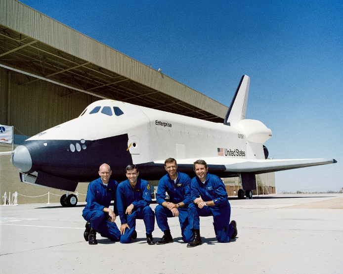 The four test pilots in their blue flight suits are kneeling in front of the space shuttle orbiter Enterprise on an airport tarmac.