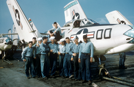 Color photo of ten men posed in front of a Grumman F9F-6 Cougar airplane on the flight deck with wings folded up, other airplanes visible in background.