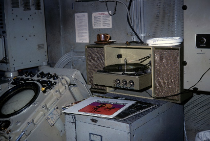 Colored image of record player and records placed on top of a filing cabinet, next to a radar set with round screen.