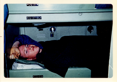 Color photo of man lying in berthing bunk with left forearm resting on his forehead, locker visible behind him.