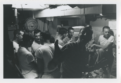 Black and white image of nine men inside a stateroom, they are standing or seated in circles talking, one man poses and smiles for the camera.
