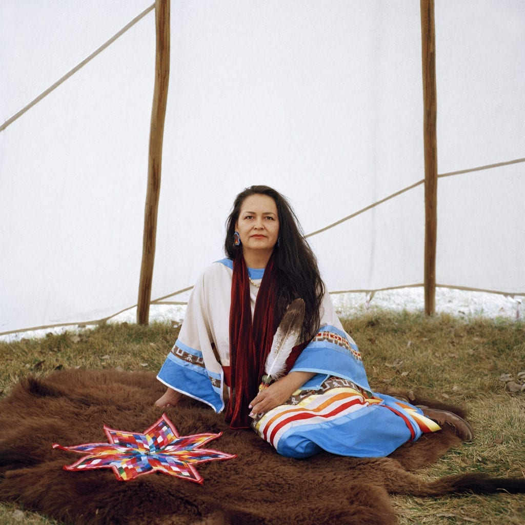 Tracey George Heese, 42, sits on buffalo skin in a tipi
