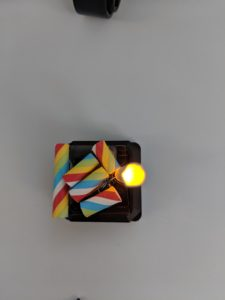 A black plastic cube with battery and a yellow led light inside. Ths top is decorated with colorful paper rolls.