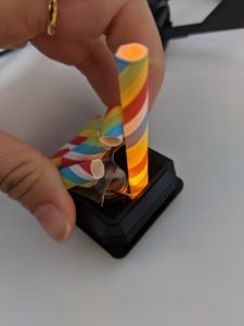 A black plastic cube with battery and led light inside. The top was covered in plastic and decorated with colorful paper rolls